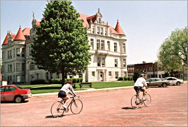 Bicyclists ride by the courthouse in Adel, Iowa.