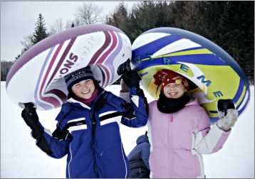 Two young girls head up the tubing hill at Afterglow resort.