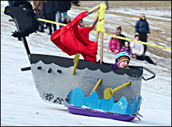 An art sled flies down the hill.
