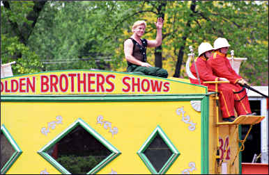 A strong man waves from a circus wagon.