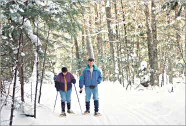 Snowshoers walk through the snowy forest near Bear Paw Outdo