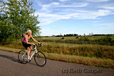 A bicyclist pedals on the Old Abe State Trail.