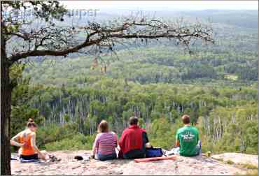 A family of hikers enjoys the view from Carlton Peak.