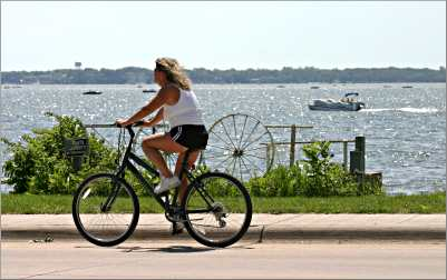 A bicyclist rides along the shore of Clear Lake.