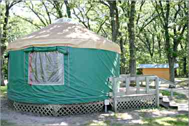 A green canvas-sided yurt looks over Clear Lake in Iowa.