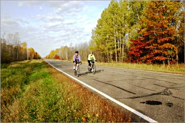 Two bicyclists pedal on the Tour de Cuyuna in fall.
