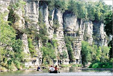 Canoeists paddle at the foot of cliffs on the Upper Iowa.