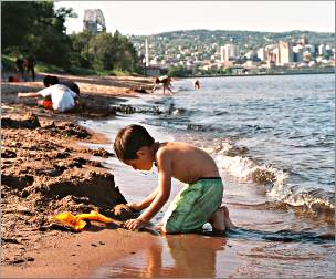 A boy plays in the sand on Park Point.