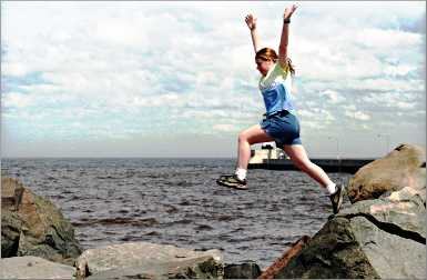 A girl jumps over rocks on Duluth's Canal Park.