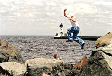 A boy jumps from rock to rock on the shore in Duluth's Canal