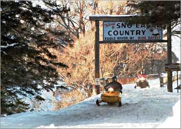 Snowmobiles roar toward Eagle River.