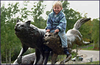 A child on a wolf sculpture in Ely.