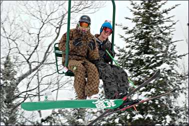 A skier and snowboarder on a chairlift.