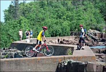 Kids ride on the Grand Marais breakwall.