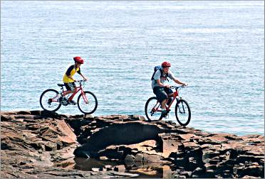 Kids ride on the harbor rocks in Grand Marais.