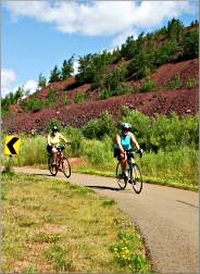 Bicyclists pedal past slag on the Mesabi Trail.