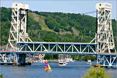 boats sail under lift bridge in Houghton, Mich.