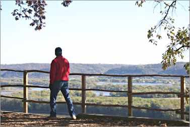 A hiker enjoys the view from Effigy Mounds in Iowa.