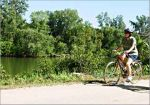 A bicyclist rides along the Red Cedar River.