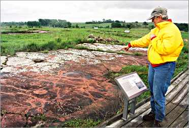 A visitor at the Jeffers Petroglyphs points to the mysteriou