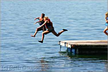 children jumping off raft at Minnesota resort.