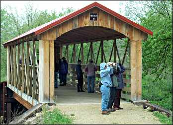 Birders on a covered bridge.