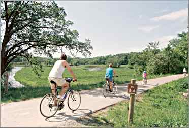 Bicyclists pass an oxbow bend of the Root River on the trail