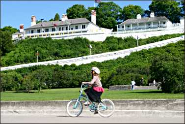 A bicyclist rides by Fort Mackinac.
