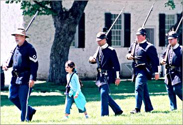 A little visitor marches with soldiers at Fort Mackinac.