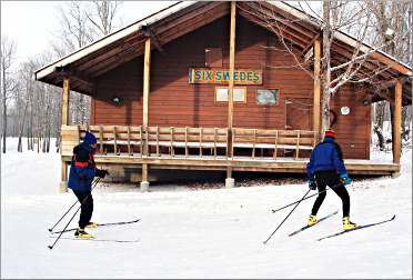 Skiers glide by the Six Swedes cabin at Maplelag.