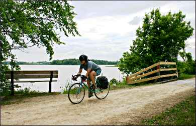 A bicyclist passes Oak Lake on the Luce Line.