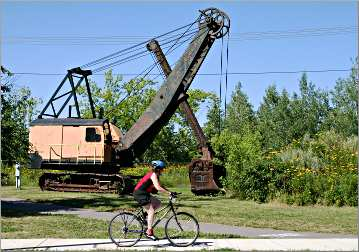 A bicyclist and steam shovel on the Mesabi Trail.