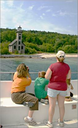 Tour-boat passengers look at Munising's Grand Island Light.