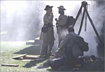 Confederate re-enactors smoke around a fire at Norskedalen.