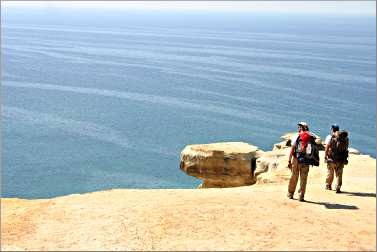 Backpackers stand on a cliff at Pictured Rocks.