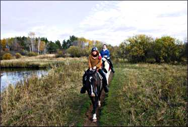 Friends ride horses near Pine River.