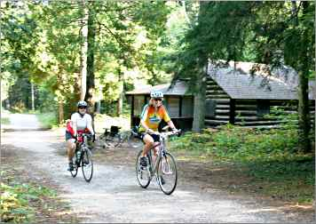 Bicyclists pass a pioneer cabin in Point Beach State Forest.