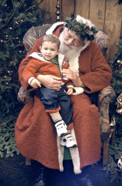 Father Christmas with child on his lap.