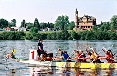 A dragon boat races past Fairlawn Mansion in Superior.