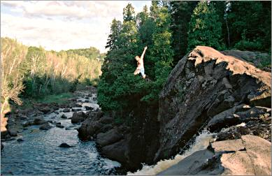 A cliff jumper leaps off Illgen Falls.