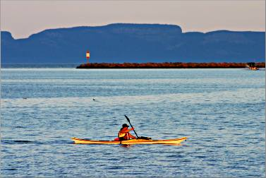 A kayaker paddles off Thunder Bay's marina.