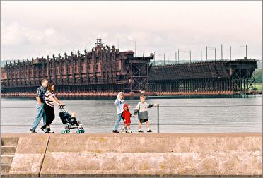 A family walks along the Two Harbors breakwall.
