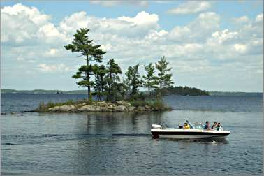 A boat speeds past an island on Rainy Lake in Voyageurs Nati
